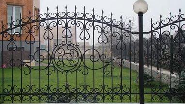 Забор из кованых элементов и металлических столбов