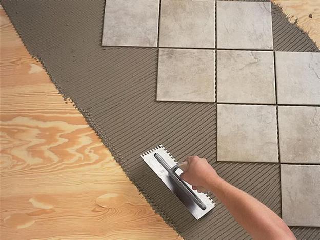Процесс укладки плитки на деревянный пол