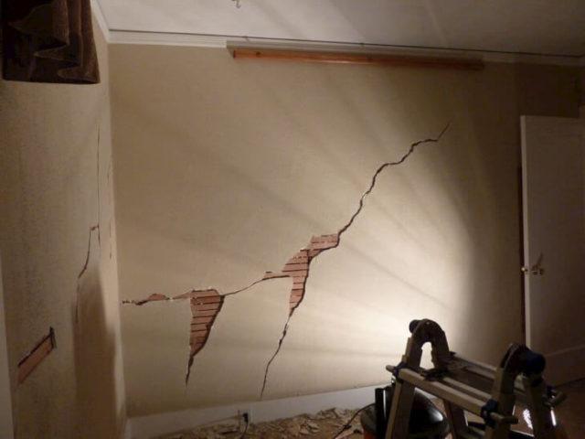 Большая трещина в штукатурке на стене в комнате