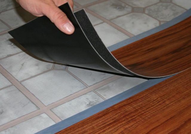 Одним из достоинств самоклеящегося винилового ламината является укладка без демонтажа прошлого покрытия. На иллюстрации изображена укладка самоклеящегося ламината на линолеум