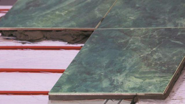 На фото процесс монтажа стержневого теплого пола в слой плиточного клея