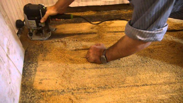 Процесс выравнивания деревянного пола с помощью электрорубанка
