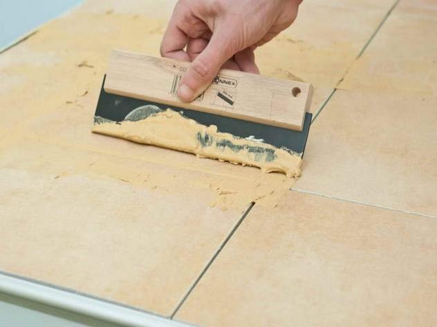 На фото показан процесс затирки плитки резиновым шпателем. Излишки материала сразу убирайте сухой губкой или тканью.