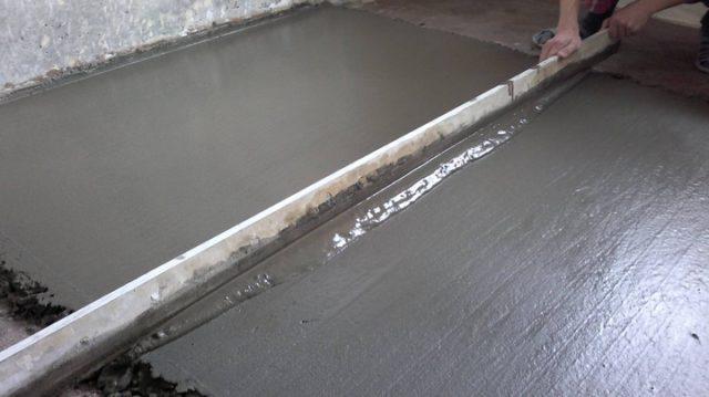 Выравнивание бетонной стяжки с помощью правила