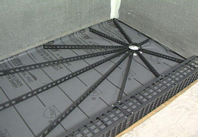 При помощи специальных направляющих формируется уклон в полу. Обратите внимание на гидроизоляцию, которая укладывается частично на стены для создания своеобразного корыта.